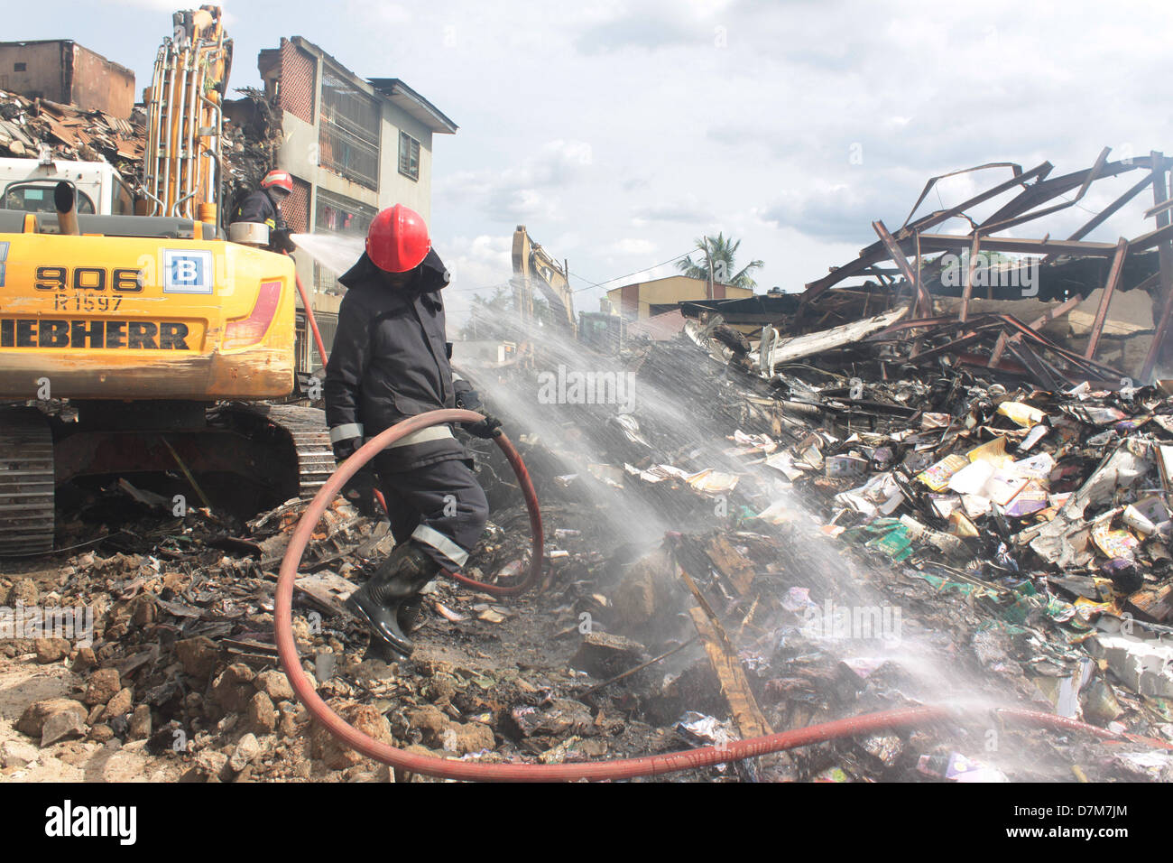 Fire officers putting out smoulder at the site of a recent aircraft crash at the outskirt of Lagos, Nigeria. - Stock Image