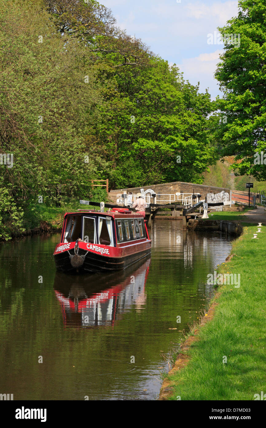 Narrow boat passing through lock gates on the Huddersfield Broad Canal, Huddersfield, West Yorkshire, England, UK. - Stock Image