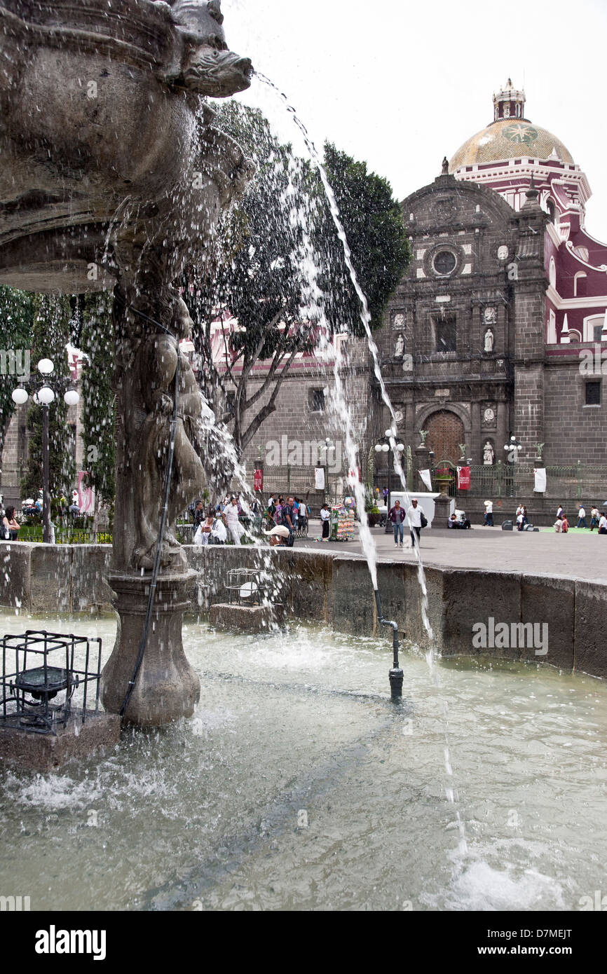 detail view carved stone fountain & refreshing splashing water with side entrance to Cathedral beyond in Zocalo - Stock Image