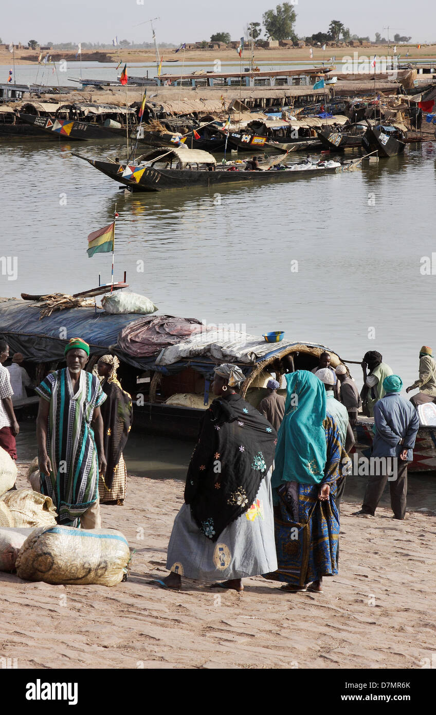 Local men and women waiting to buy fish from fishing boats, early morning, Mopti fish market on River Niger, Mali - Stock Image
