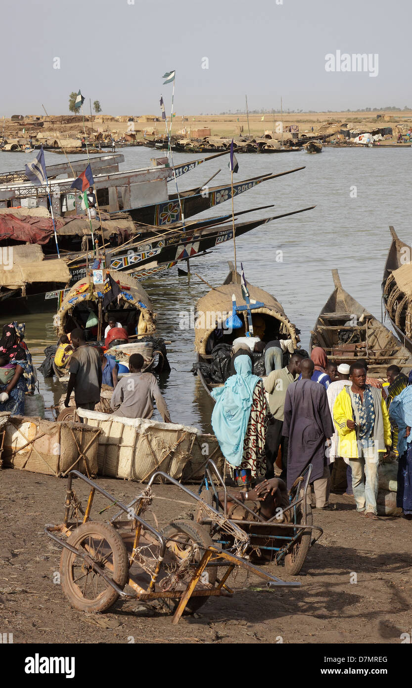 Local men and women waiting to buy fish from fishing boats, early morning, Mopti fish market on River Niger, Mali Stock Photo