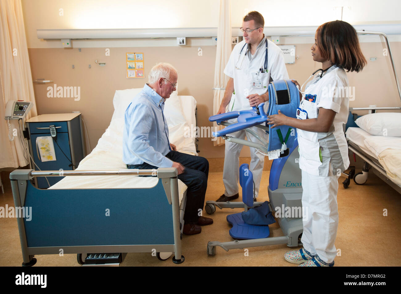 Nurses helping a patient out of bed - Stock Image