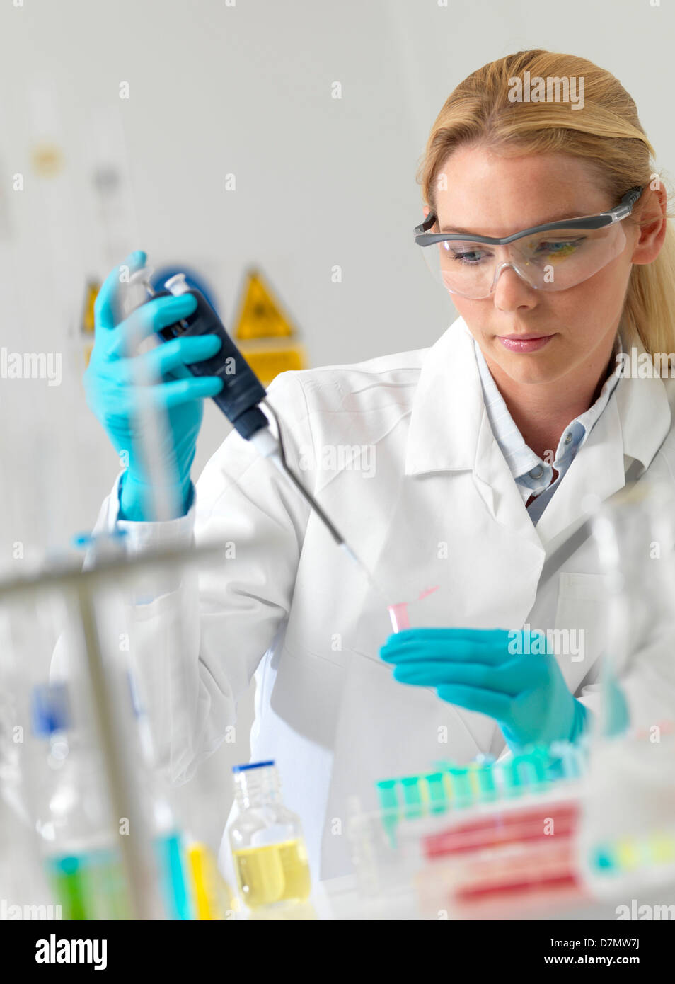 Researcher pipetting liquid - Stock Image