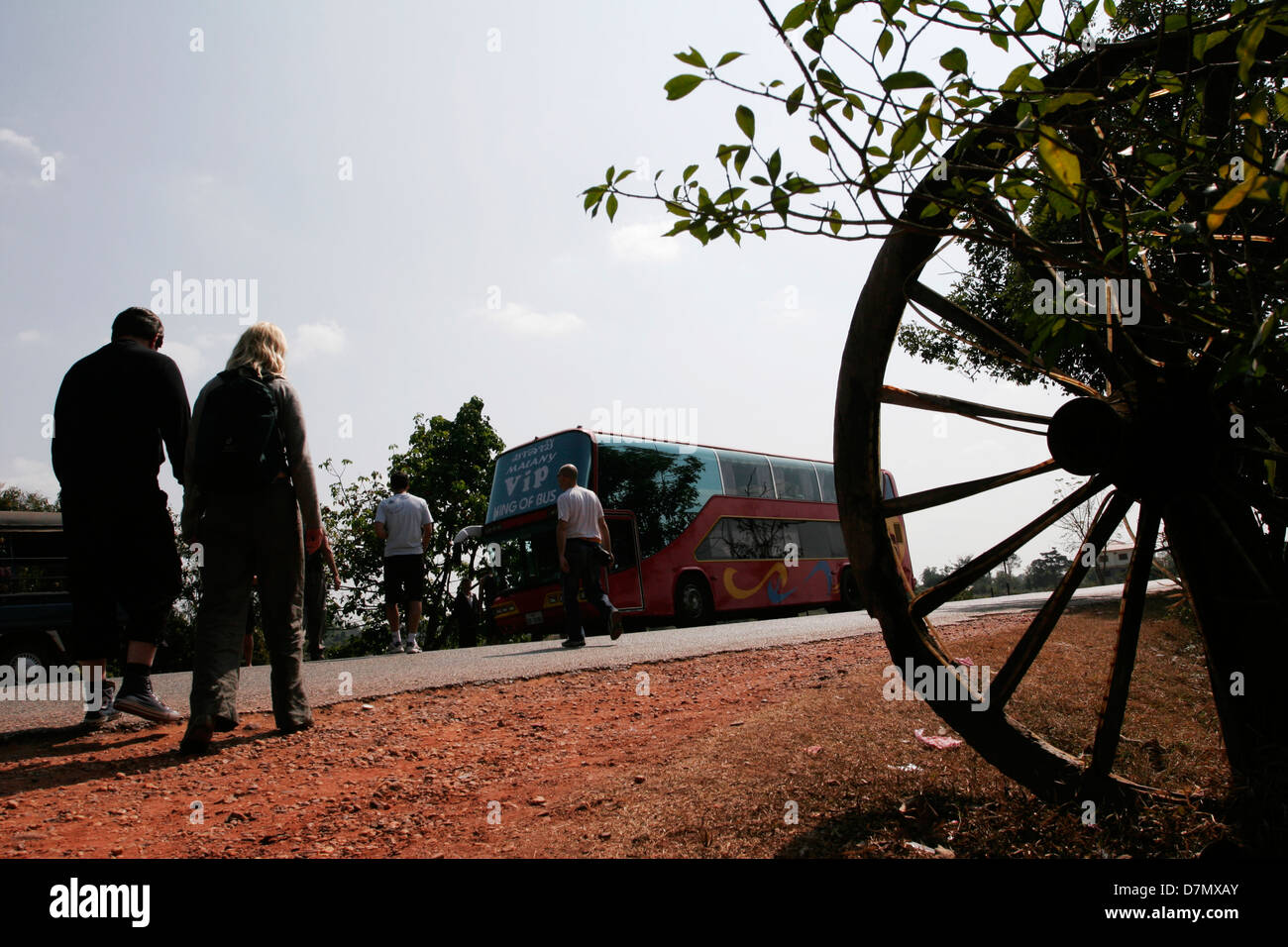 Tourists embark on their bus after a break at a road side stop between Vientiane and Van Vieng. - Stock Image