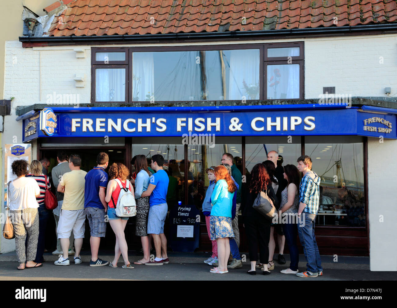 English holidaymakers queueing for Fish and Chips, Wells next the Sea, Norfolk, s people queue chip shop - Stock Image