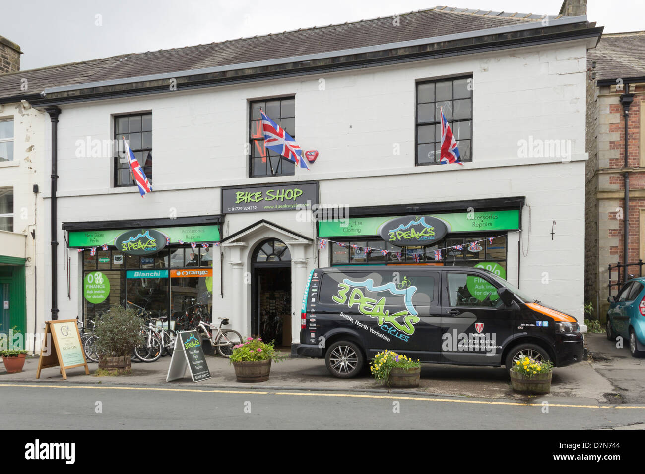 The 3 Peaks Cycles shop and company van on Market Place in Settle, North Yorkshire. - Stock Image