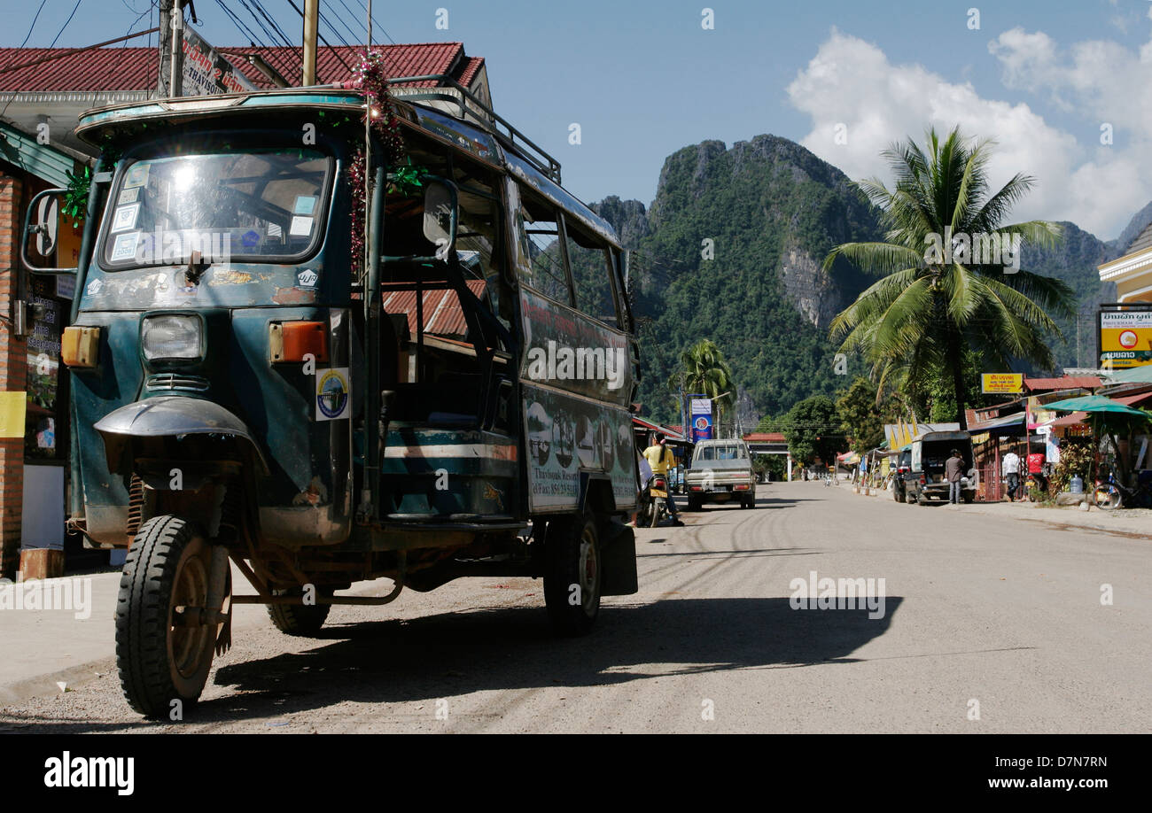 A tuk-tuk (songthaew) on the main street in Vang Vieng. - Stock Image