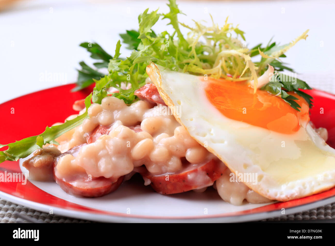 White beans with slices of sausage and fried egg - Stock Image