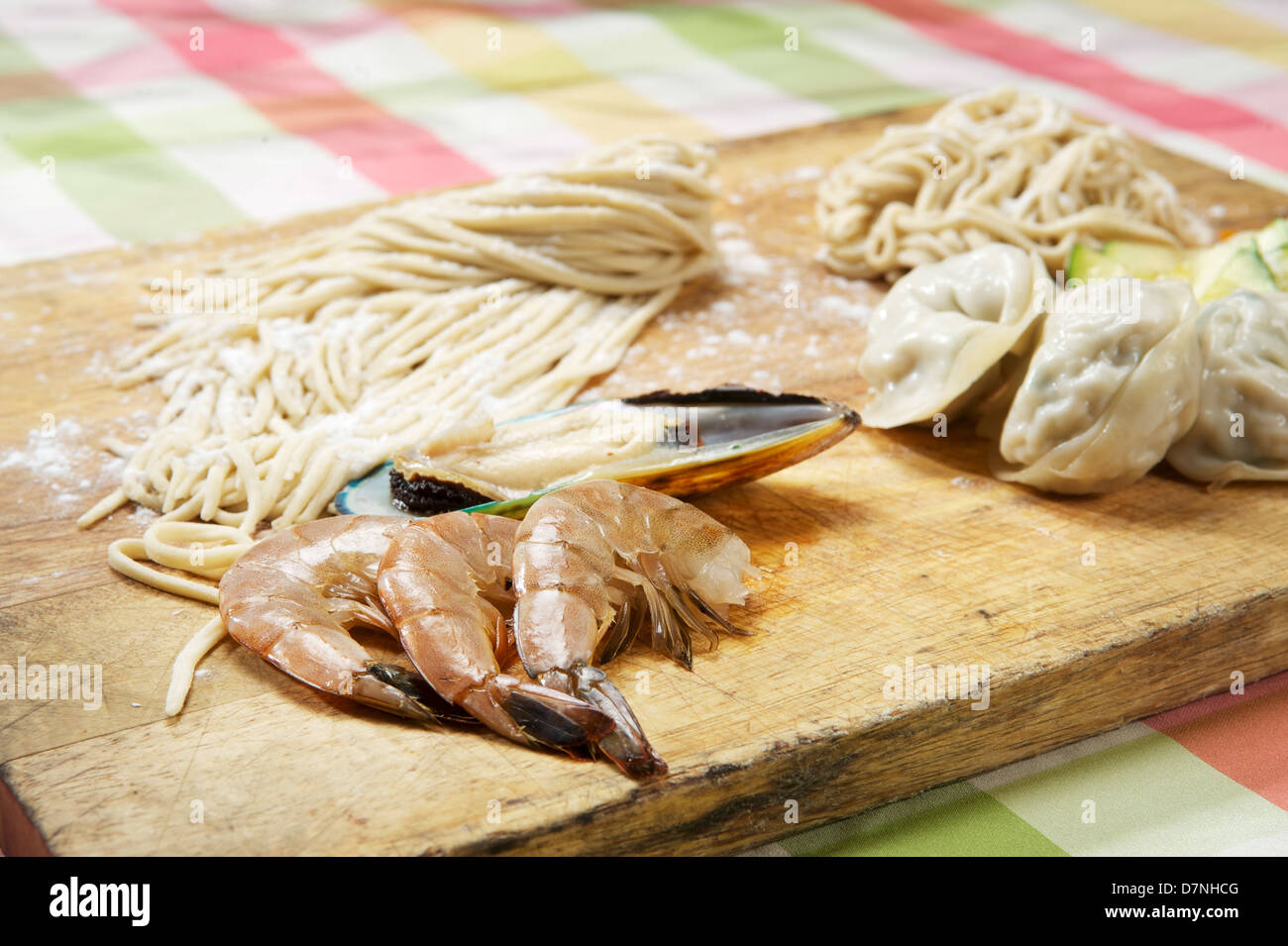 Shrimp, mussels, dim sum, and pasta on a cutting board.  Korean restaurant - Stock Image