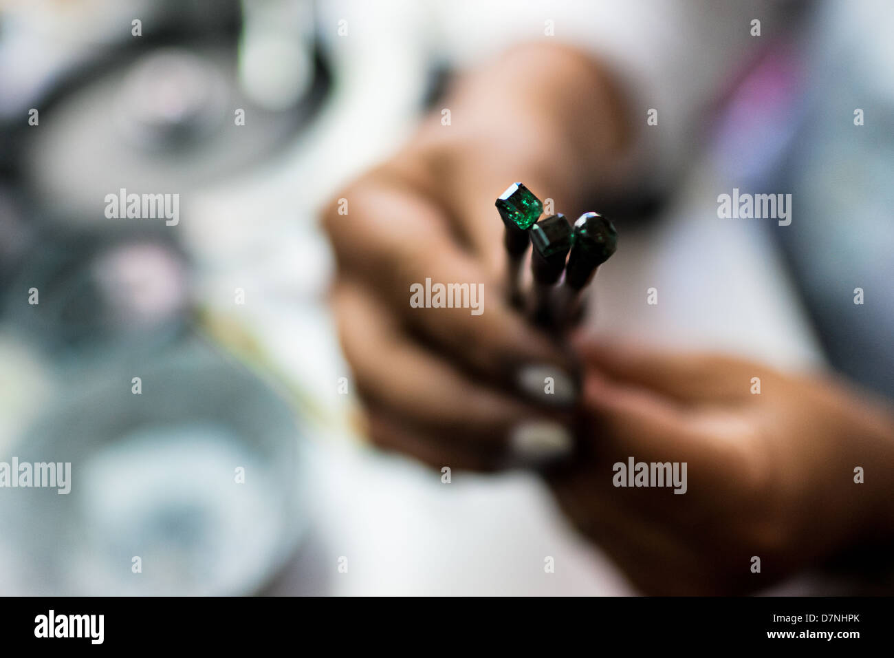 An emerald cutter shows a gemstone she is working on in a cutting and polishing workshop in Bogota, Colombia. - Stock Image