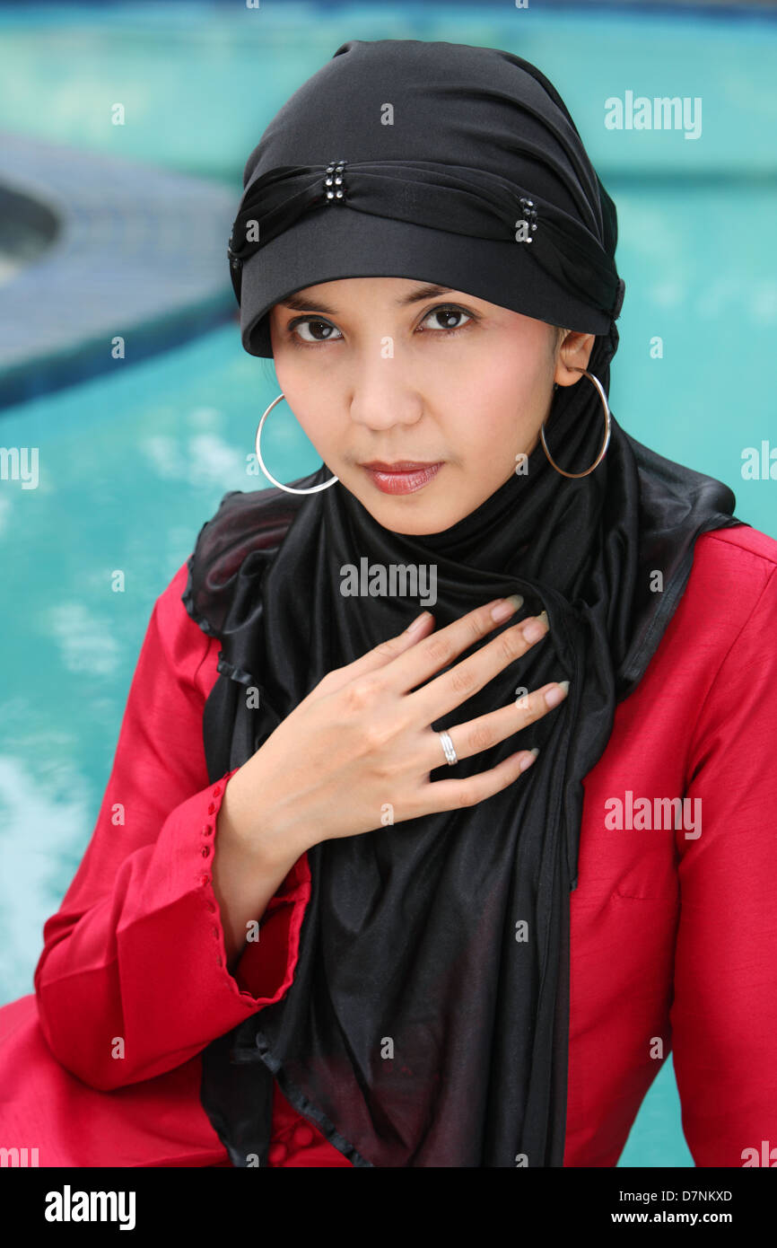 Muslim woman sitting by the swimming pool - Stock Image