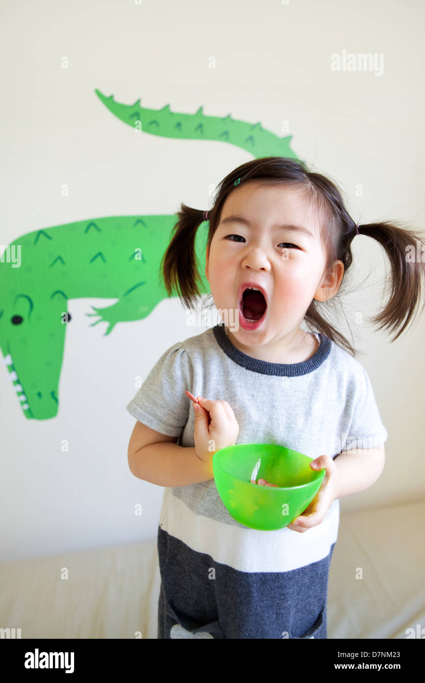 Korean American toddler in pigtails shouting to camera eating snacks from green bowl and crocodile wall art behind. - Stock Image