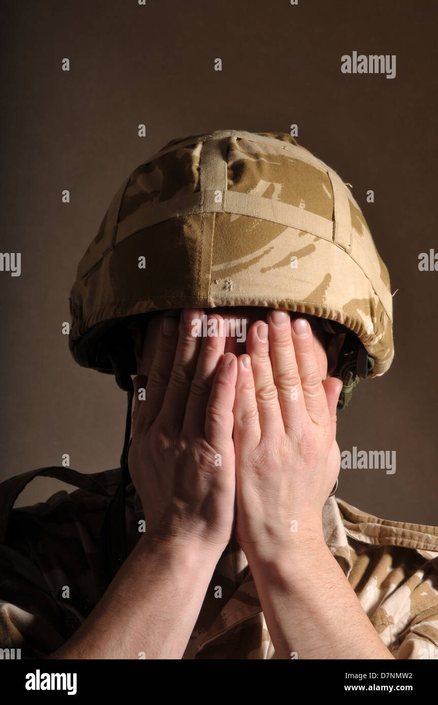 British soldier with both his hands covering his face. - Stock Image