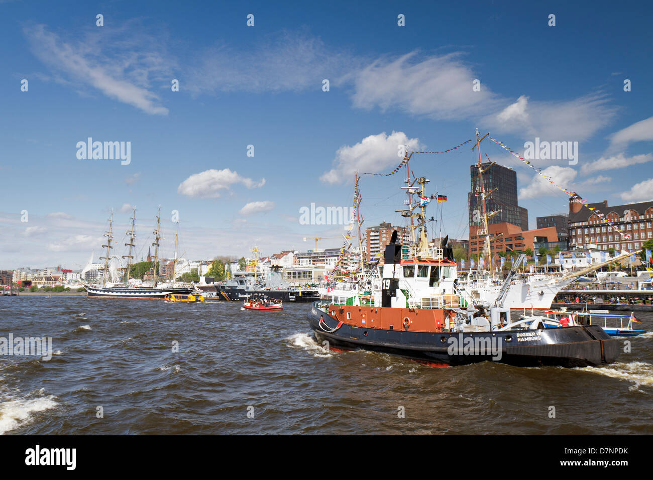 A tug sailing West along the River Elbe in Hamburg during the Hafen Geburtstag. - Stock Image