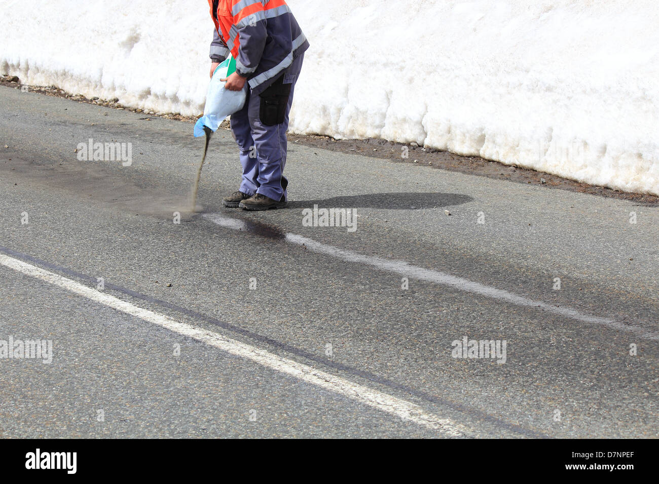 Road maintenance cleaning a Trace of oil in winter - Stock Image