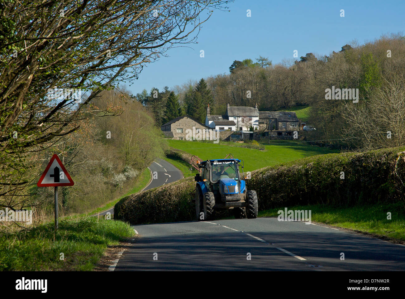Tractor on the A5074 road through the Lyth Valley, South Lakeland, Cumbria, England UK - Stock Image