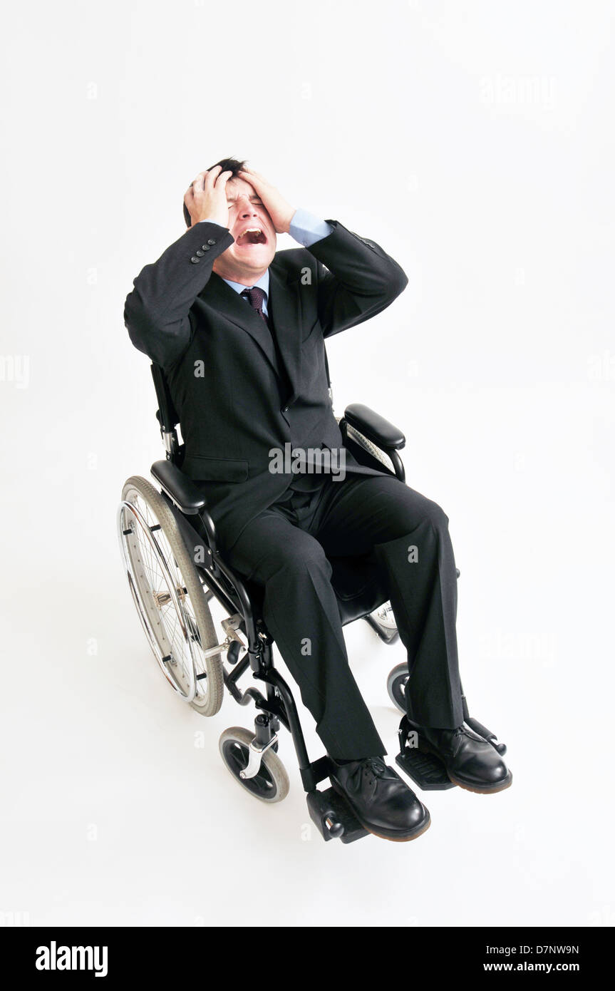 Overhead view of businessman sat in a wheelchair, with his hands on his head and screaming/shouting. - Stock Image