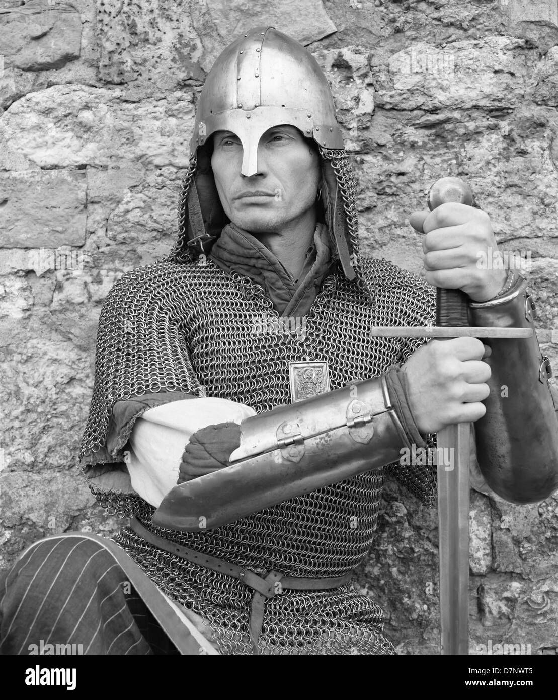 russian man in armor with a sword against the wall of stones stock