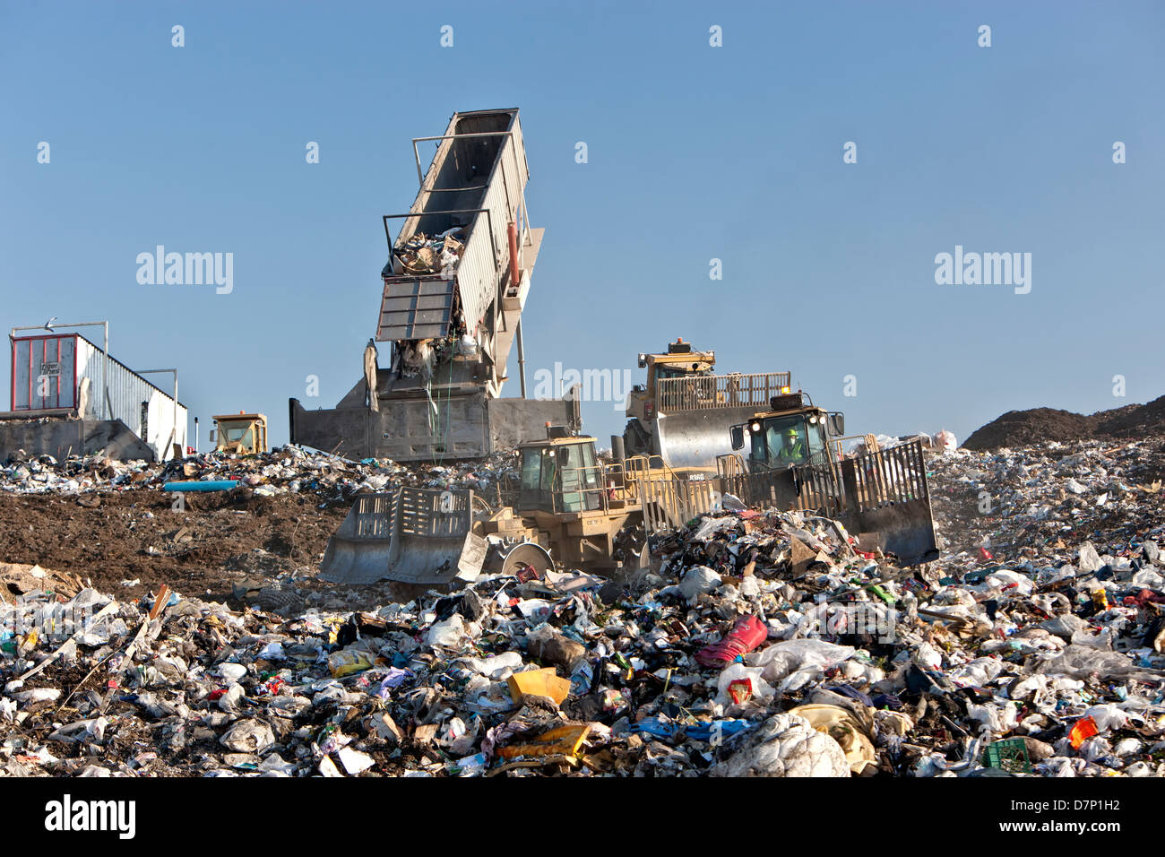 Landfill, tractor compactors pushing trash.  Tipper dumping semi trailer containing collected garbage. - Stock Image