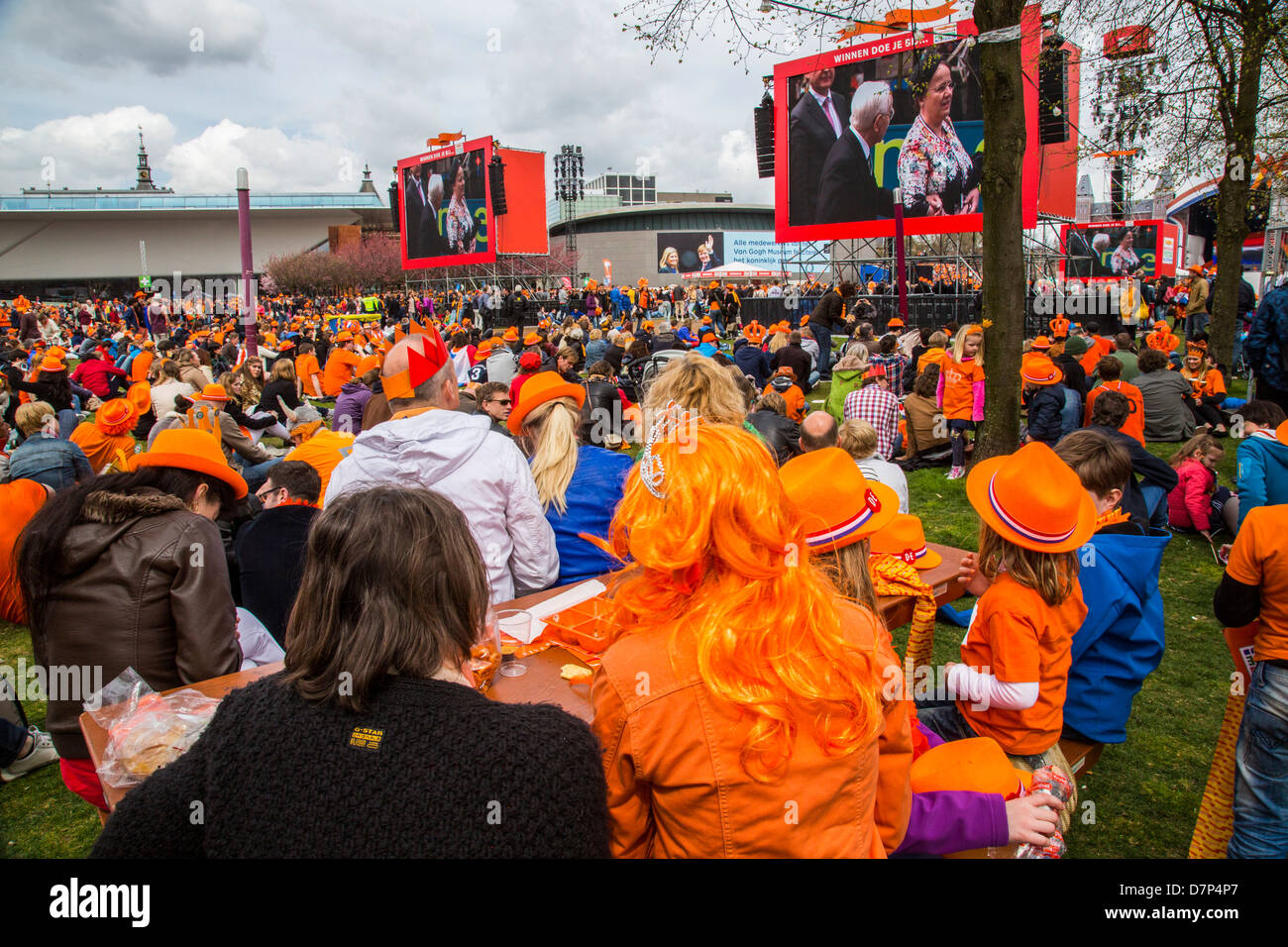 People celebrating annual Queens day on Museums Plein square in Amsterdam. Live TV coverage of enthronement of King - Stock Image