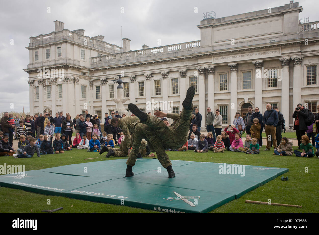 As families queue in the grounds of the Naval College, Greenwich, member of Royal Marines Commandos demonstration - Stock Image
