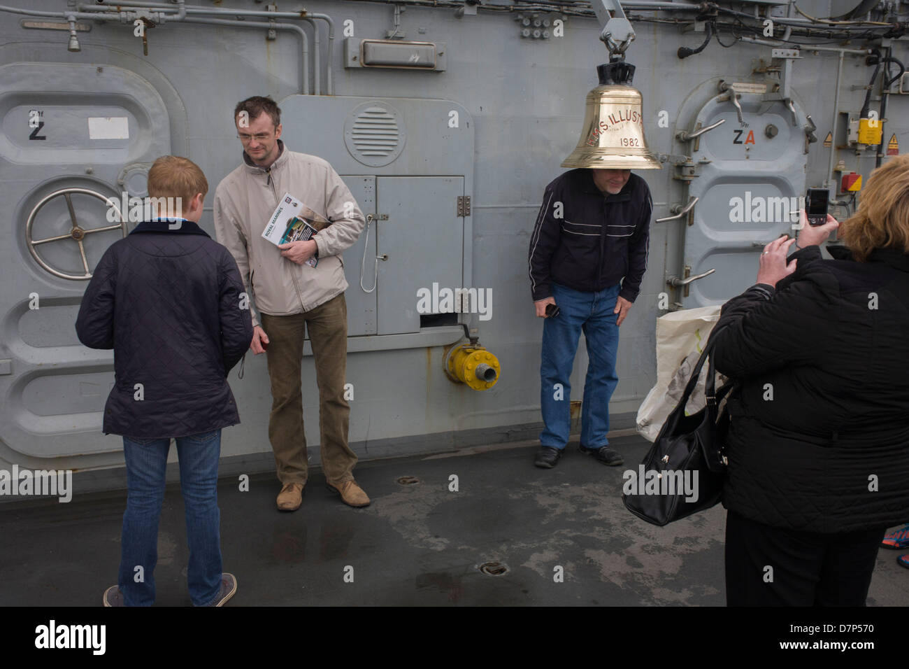 Visitors admire the ship's bell while touring the top deck on-board the Royal Navy's aircraft carrier HMS - Stock Image