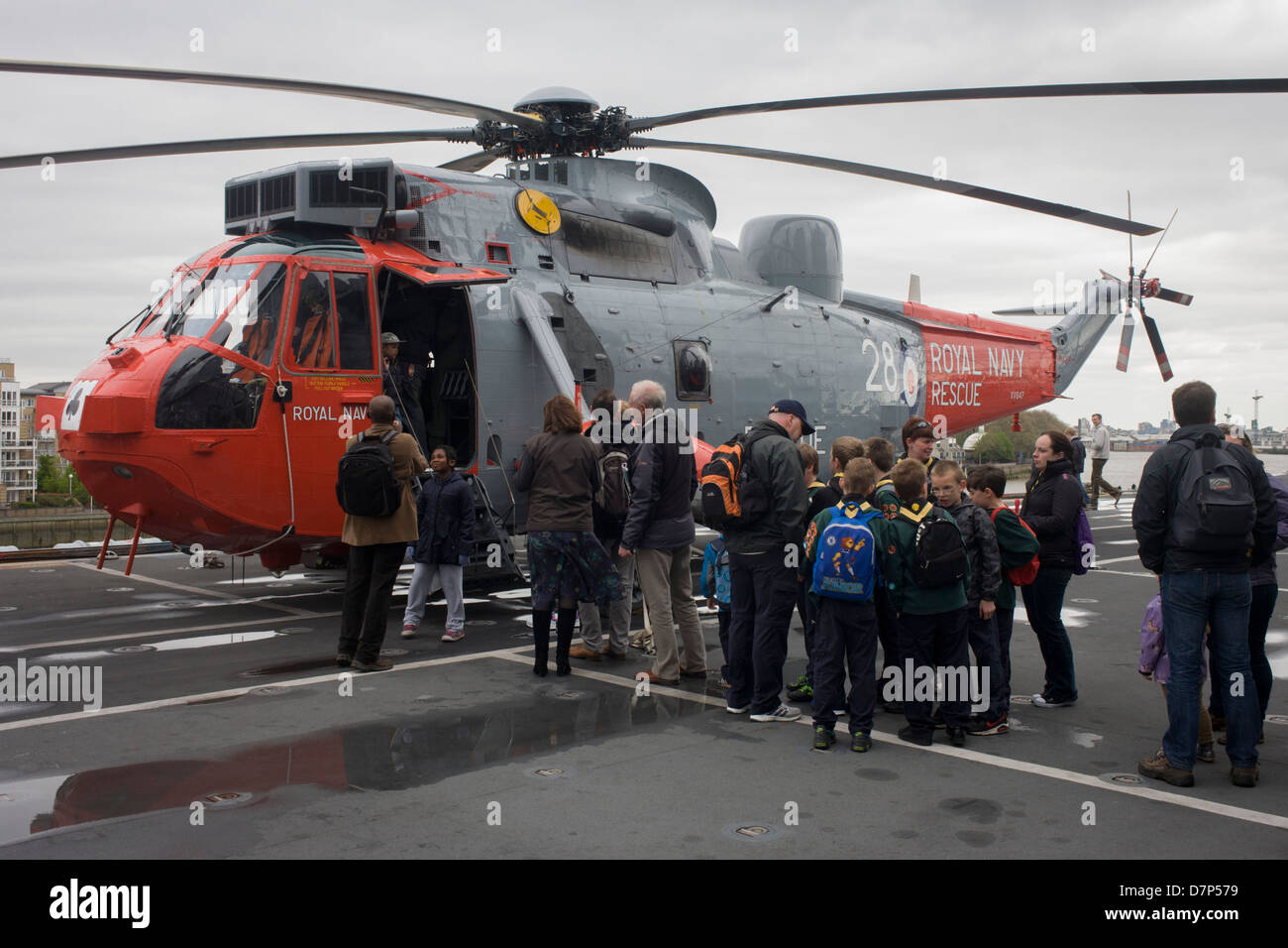 Visitors admire a Sea King helicopter while touring the top deck on-board the Royal Navy's aircraft carrier - Stock Image