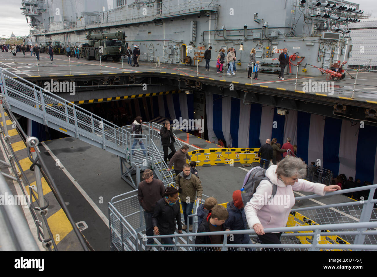Visitors climb stairs from the hangar deck to the upper top deck while touring the hangar deck on-board the Royal - Stock Image