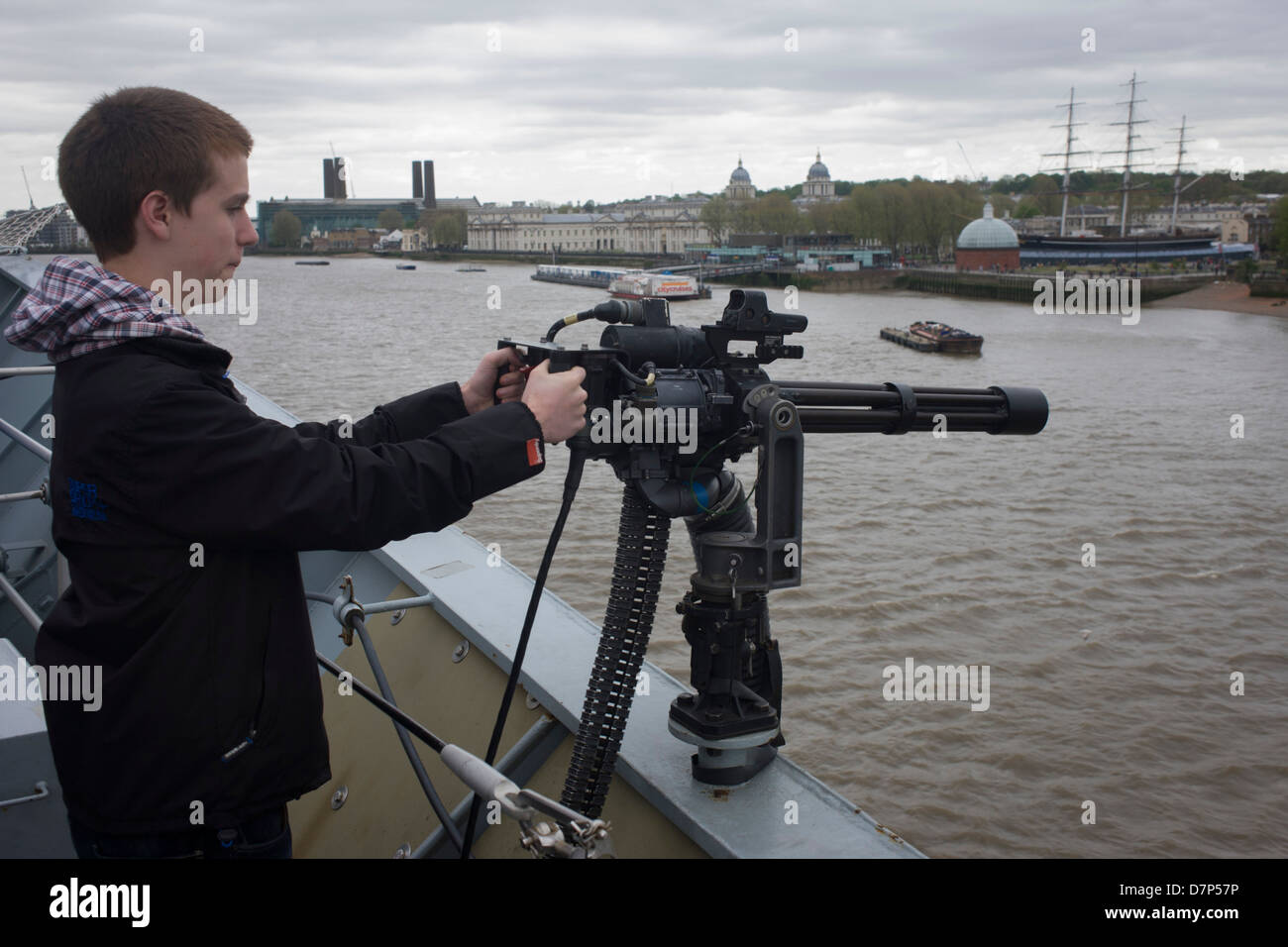 A 15 year-old teenager points a Minigun cannon from the top deck of HMS Illustrious over the river Thames at Greenwich, - Stock Image