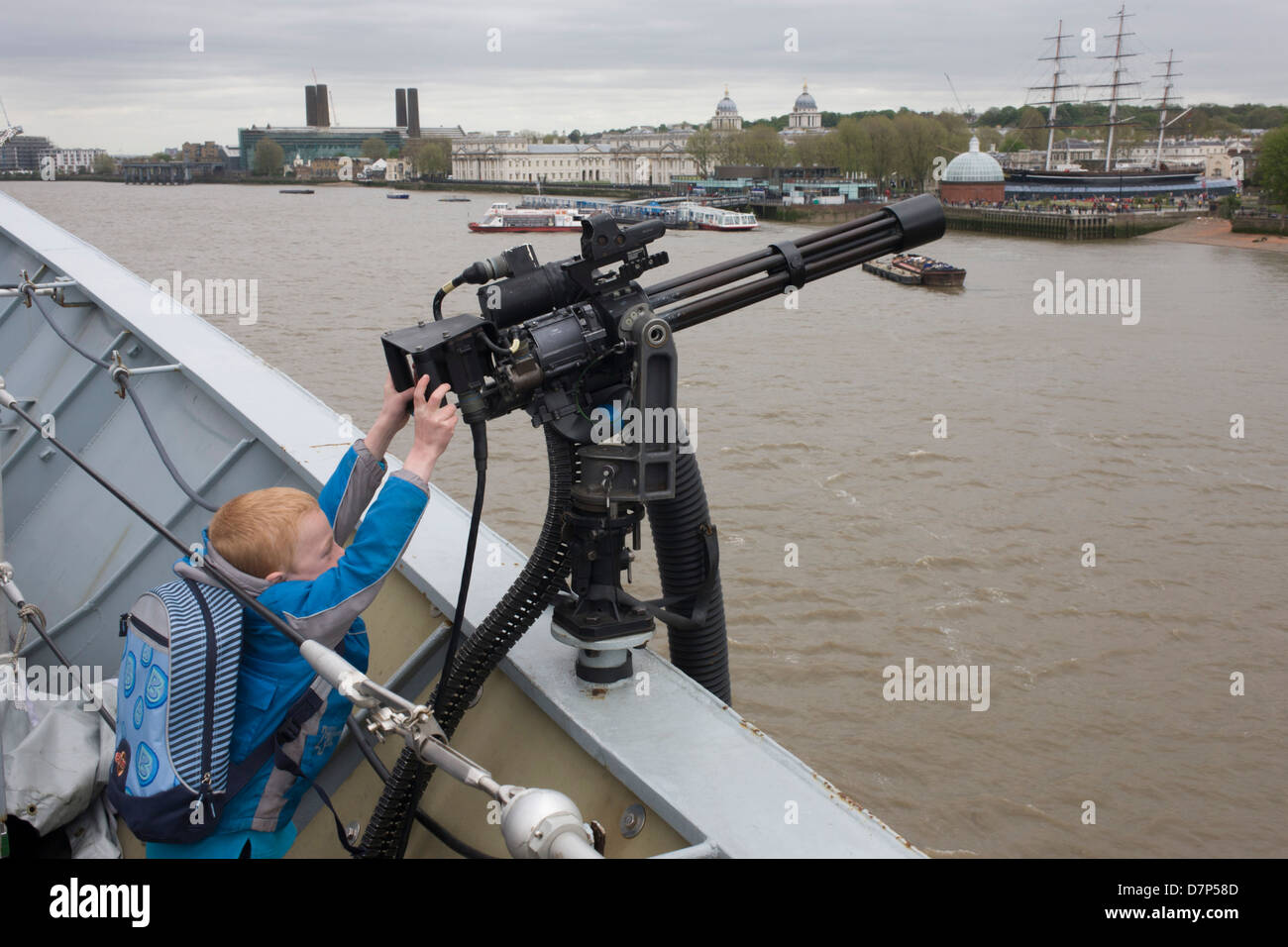 A young boy, too short to reach points a Minigun cannon from the top deck of HMS Illustrious over the river Thames - Stock Image