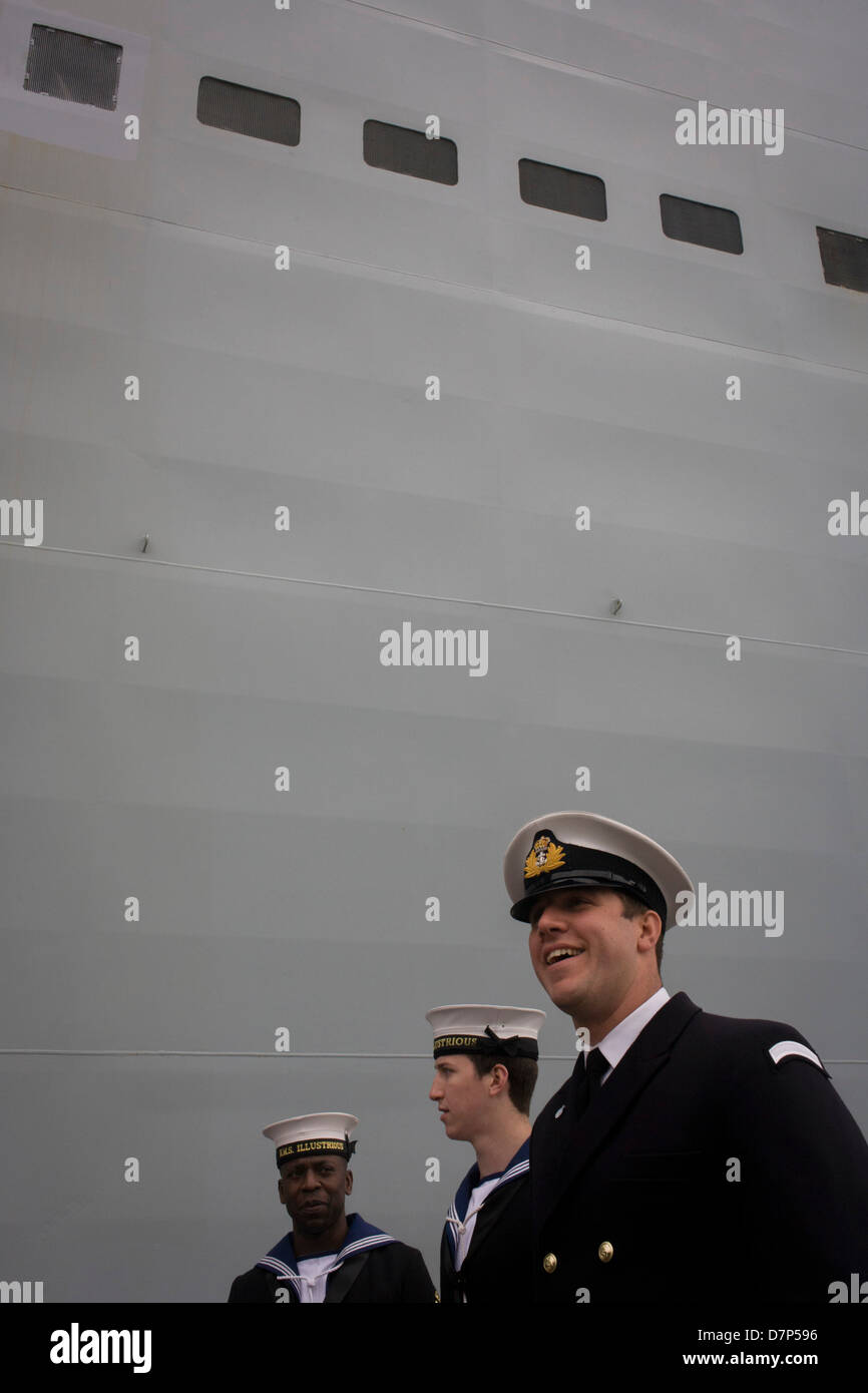Student officers and a sailor rating on duty beneath the giant hull of their ship during a tour by the general public - Stock Image