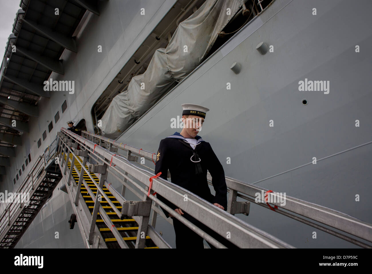 A sailor walks down the gangplank beneath the giant hull of their ship during a tour by the general public on-board - Stock Image