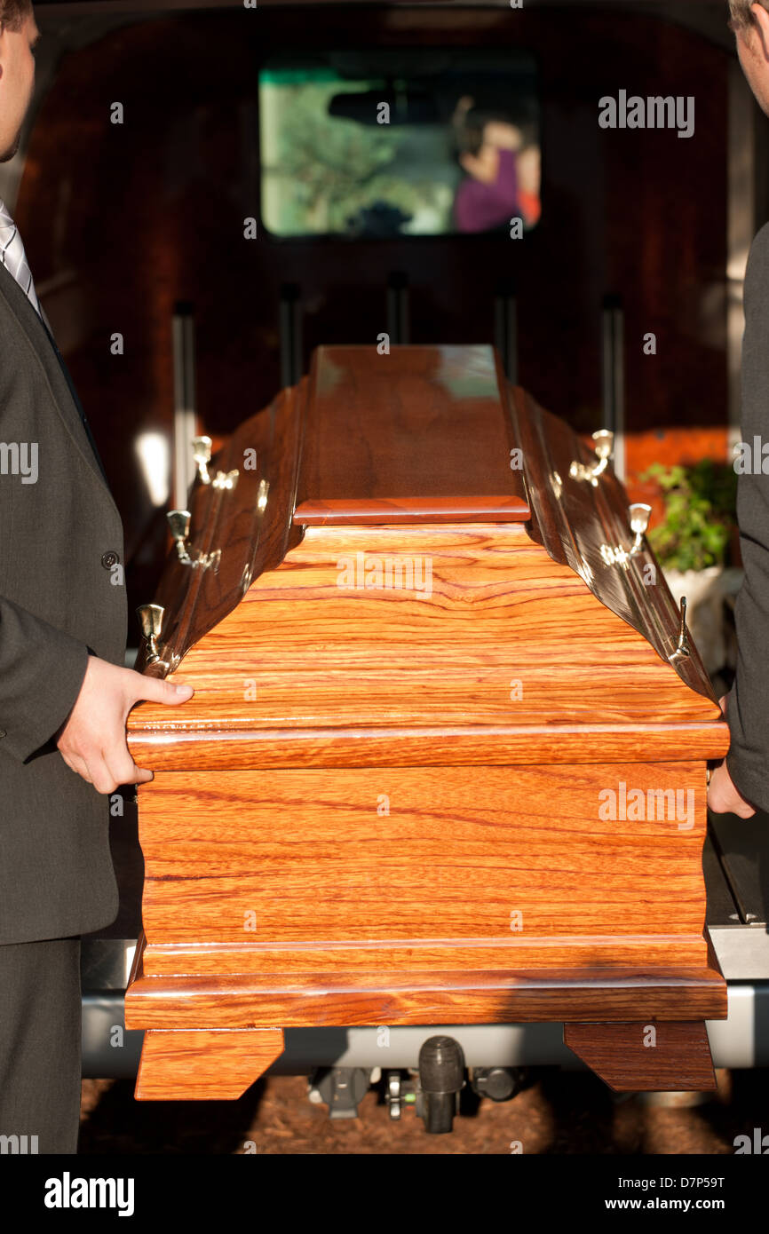 Dolor - Funeral with coffin on a cemetery, the casket carried by coffin bearer - Stock Image