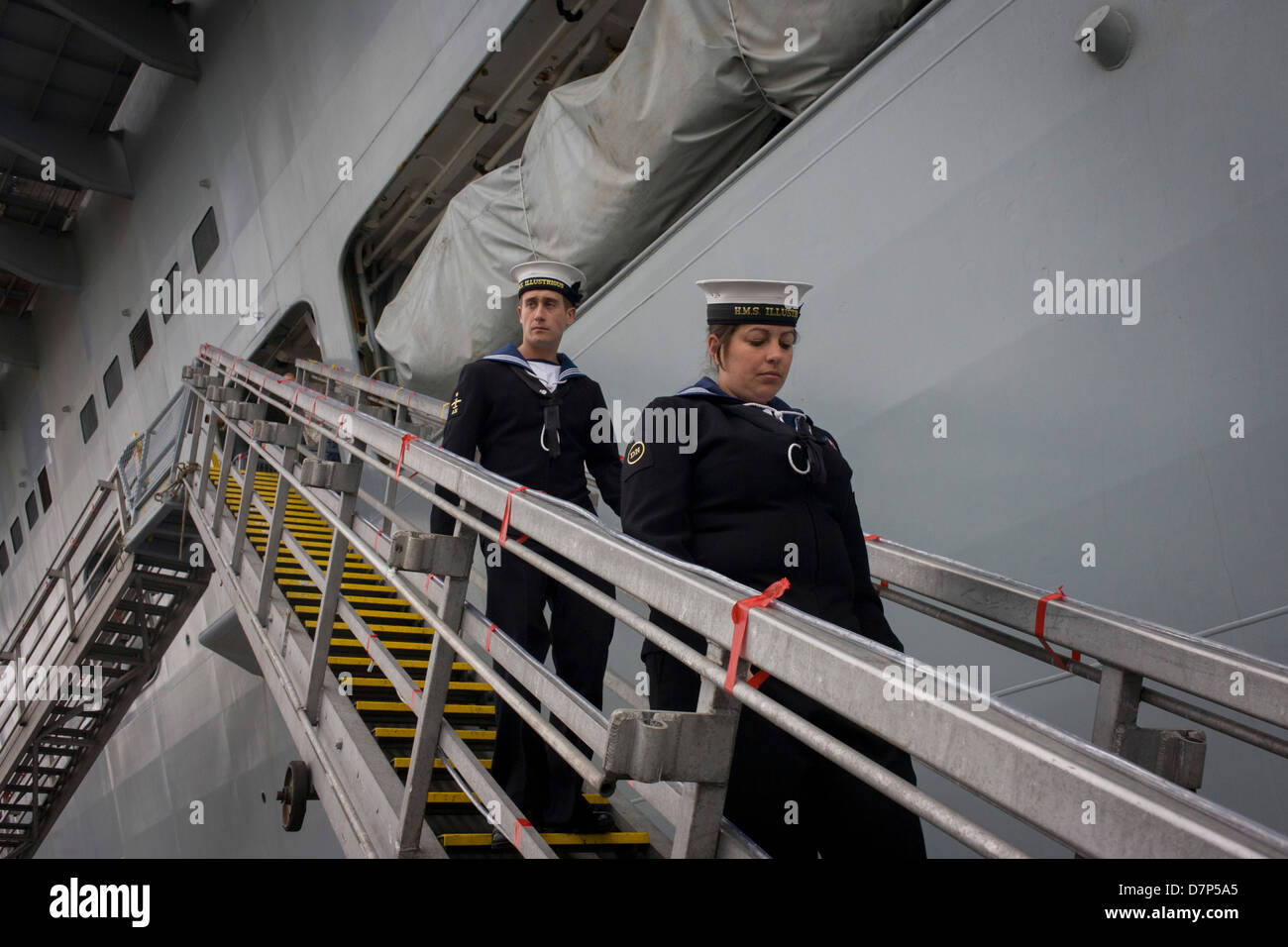 Sailors walk down the gangplank beneath the giant hull of their ship during a tour by the general public on-board - Stock Image