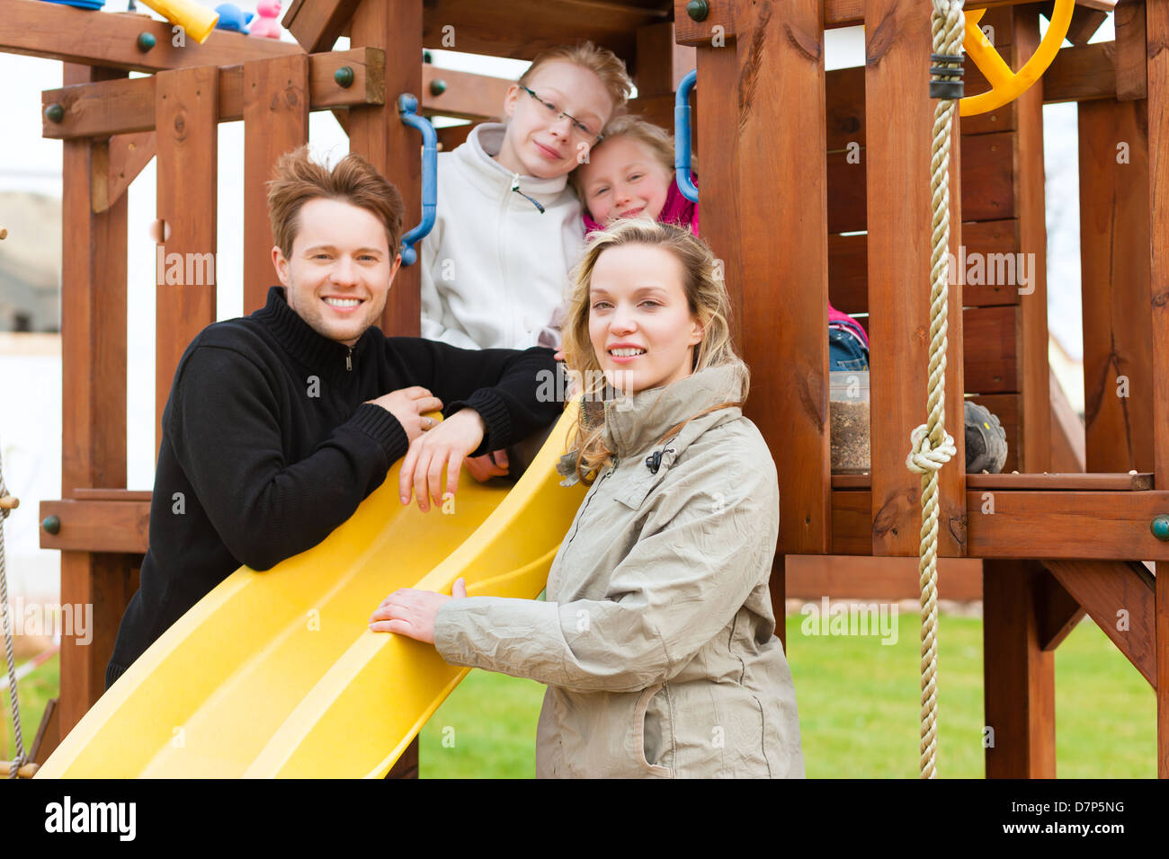 Young Family on the playground, the children sitting on a climbing frame, mother and father standing in front Stock Photo