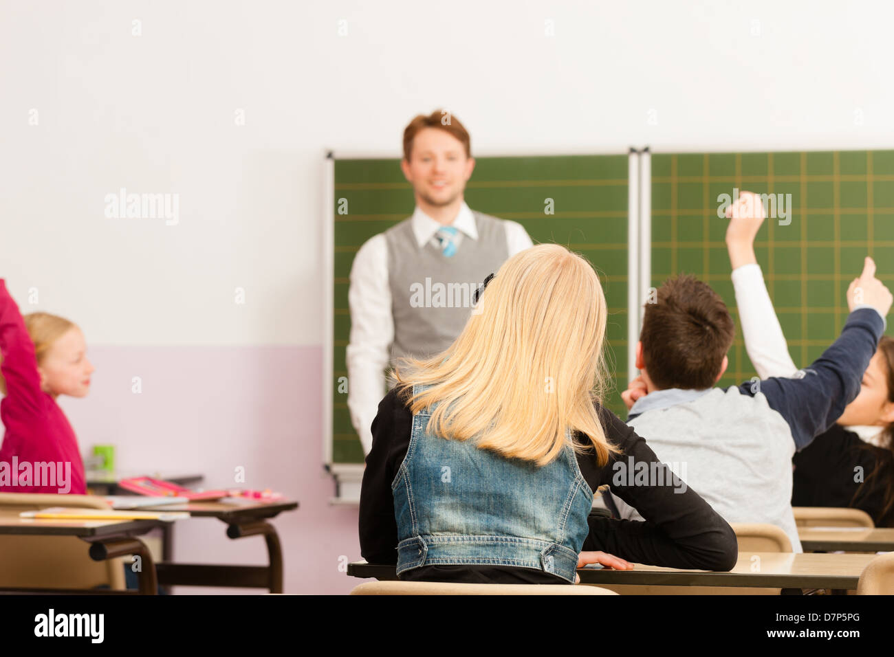 Education - Young teacher with pupil in his form of the elementary or primary school teaching - Stock Image