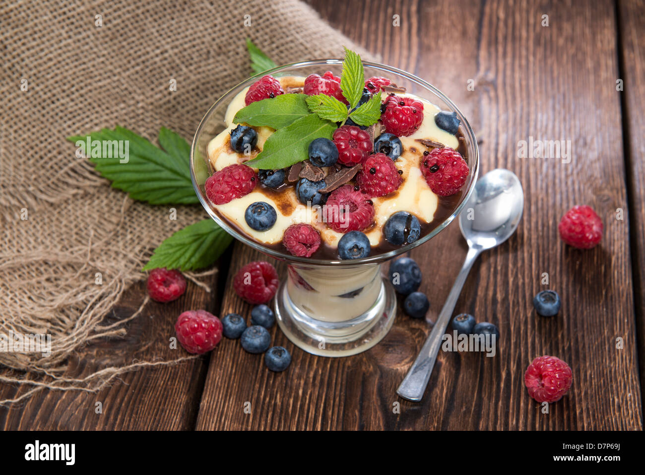 Pudding Dessert with Chocolate Sauce and fresh Berries on wooden background - Stock Image