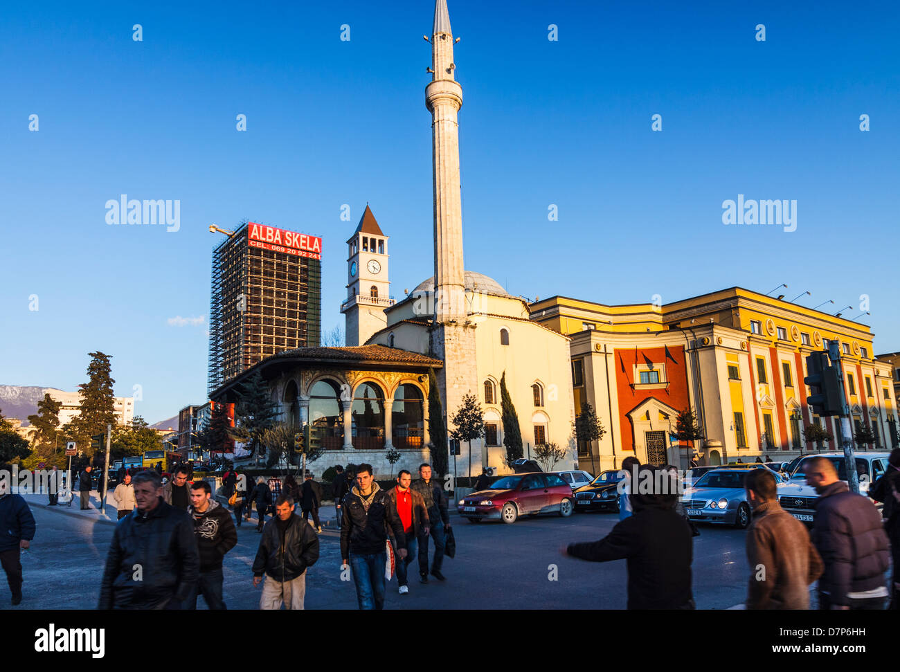 People crossing Skanderbeg Square with Ethem Bey mosque in background. Tirana, Albania - Stock Image