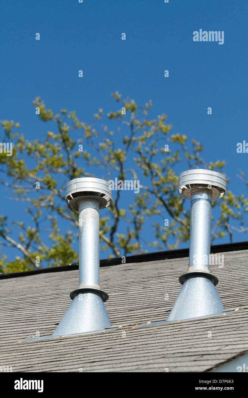 A pair of residential roof exhaust vents on a asphalt shingled house ...