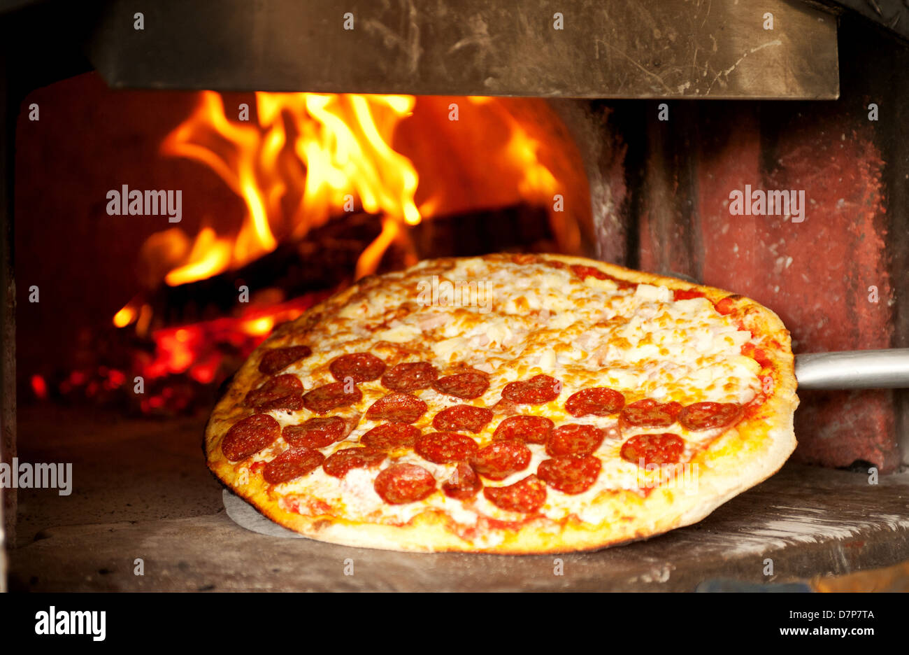 A pepperoni pizza cooks in a wood fired pizza oven. - Stock Image