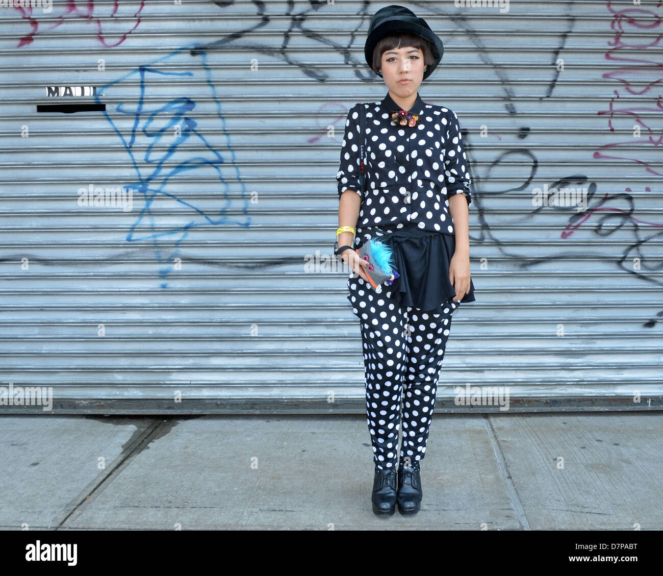 Portrait of a woman in a polka dot suit in front of a grating with graffiti in Long Island City, New York. - Stock Image