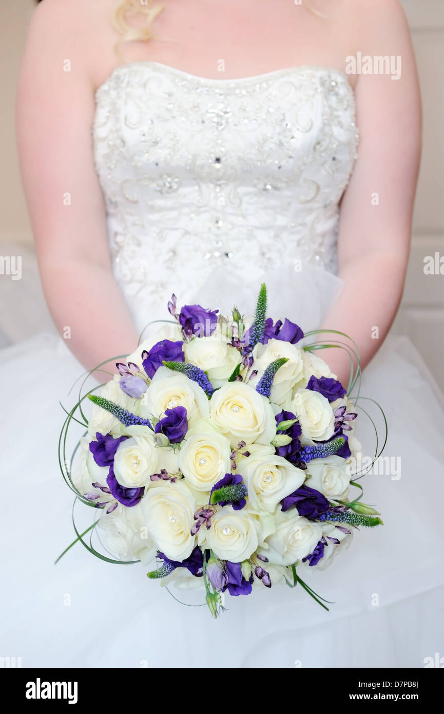 Bride holding bouquet of white and purple flowers on wedding day bride holding bouquet of white and purple flowers on wedding day showing dress detail closeup izmirmasajfo