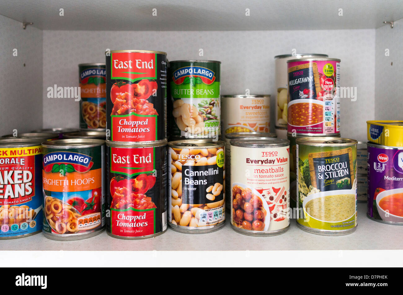 Food cans and tins on the shelf of a store cupboard - Stock Image