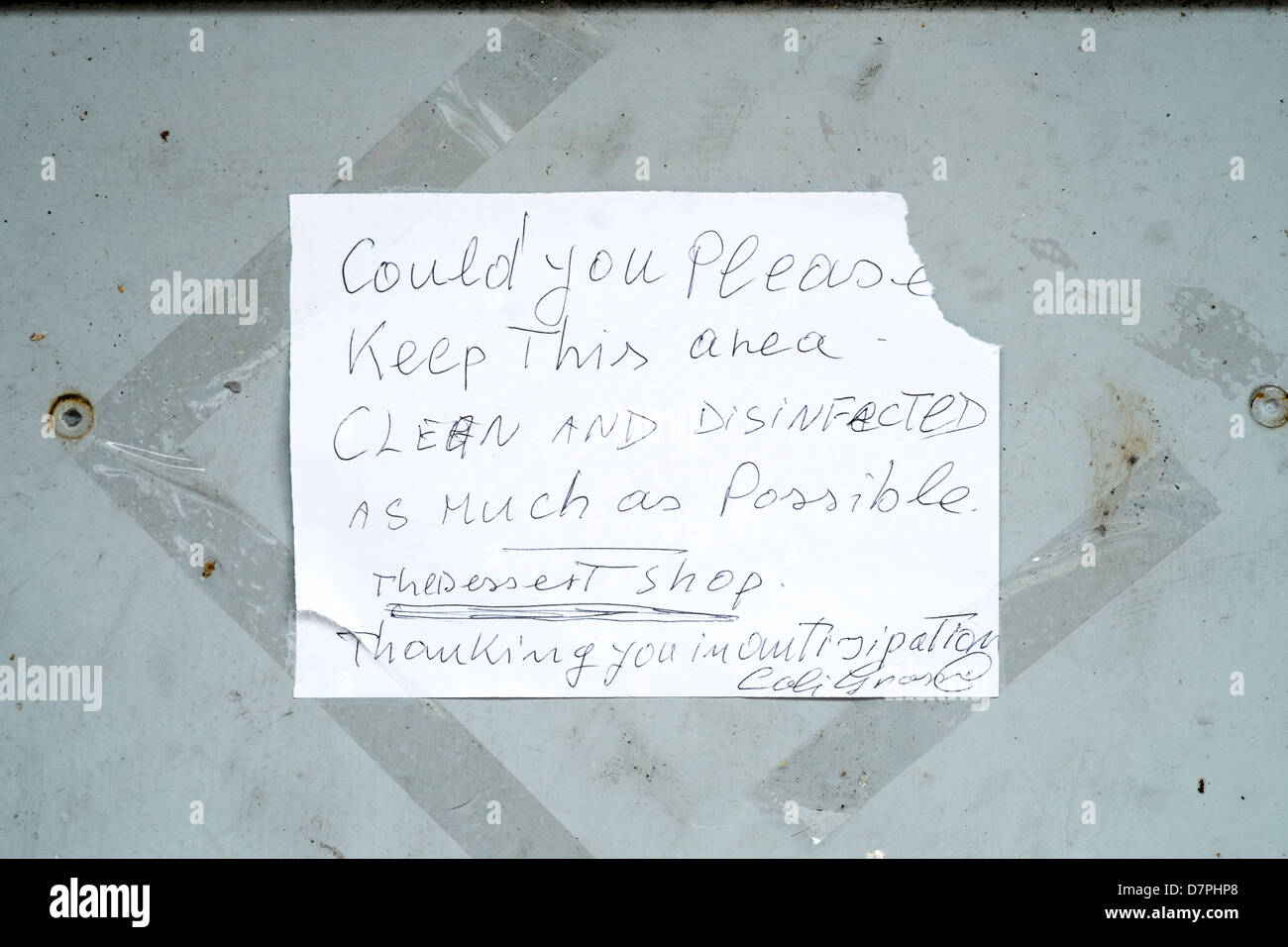 Hand written paper note with torn corner taped to a door - Stock Image