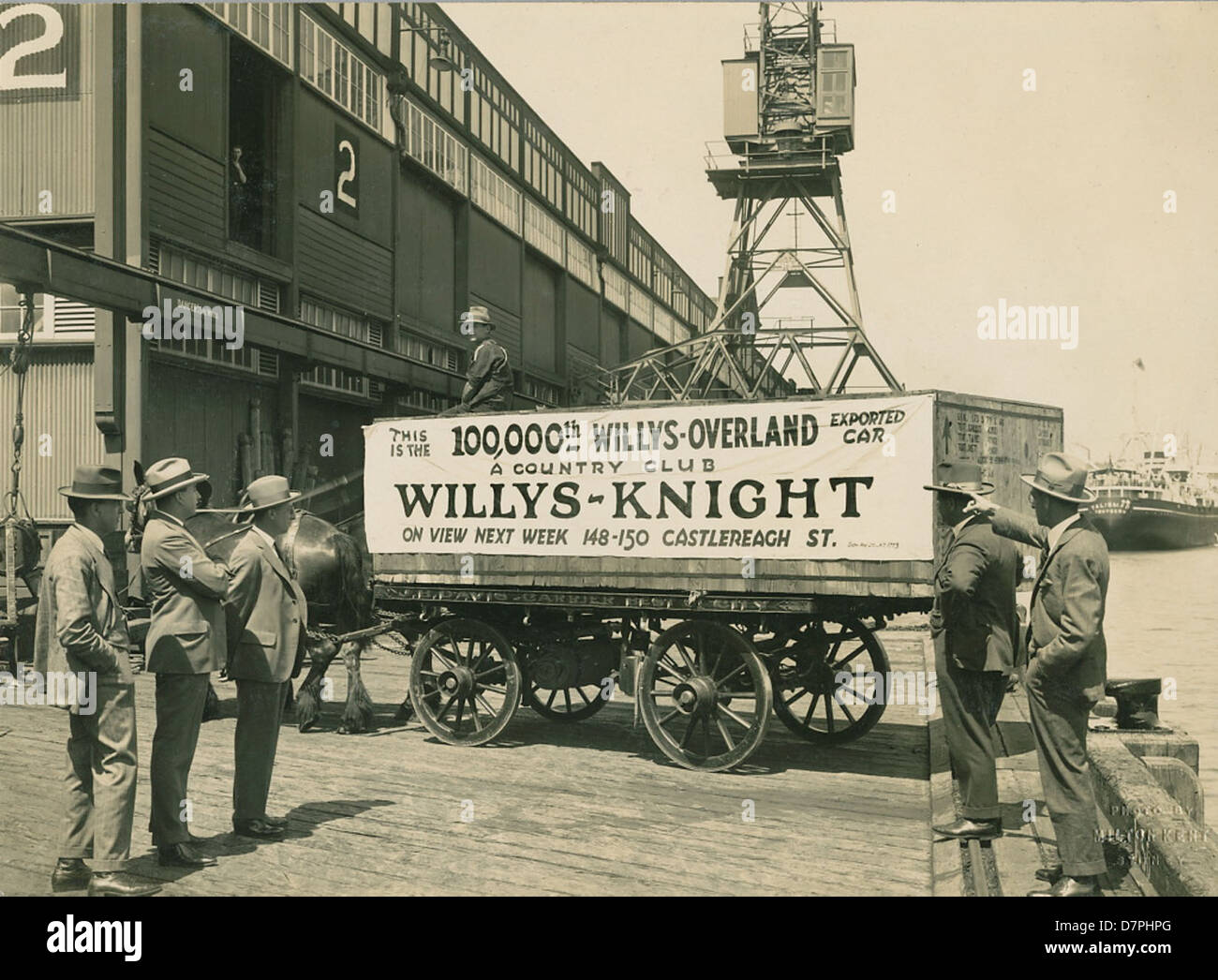 Horse and cart on wharf with crate containing the 100,000th Willys-Overland exported car, 1920 - 1929 - Stock Image
