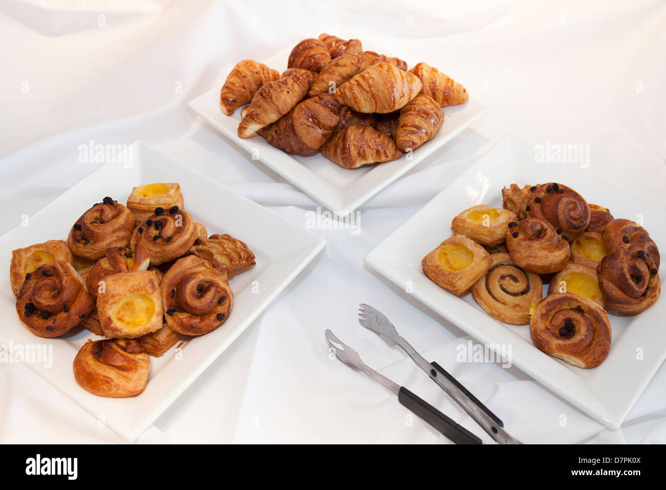 Croissants and Danish pastries on a hotel breakfast table with serving fork - Stock Image