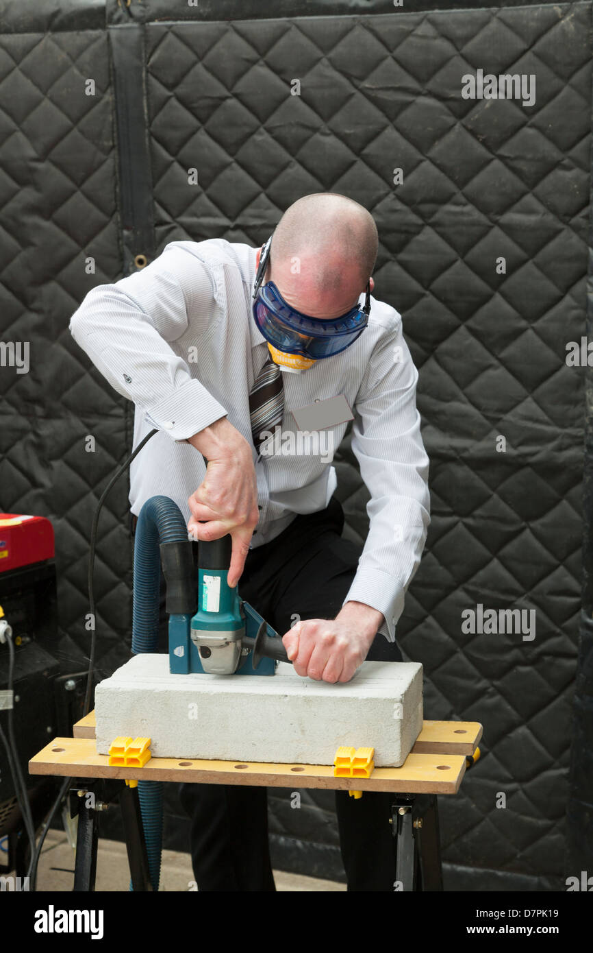 man demonstrating dust extraction on power tool - Stock Image