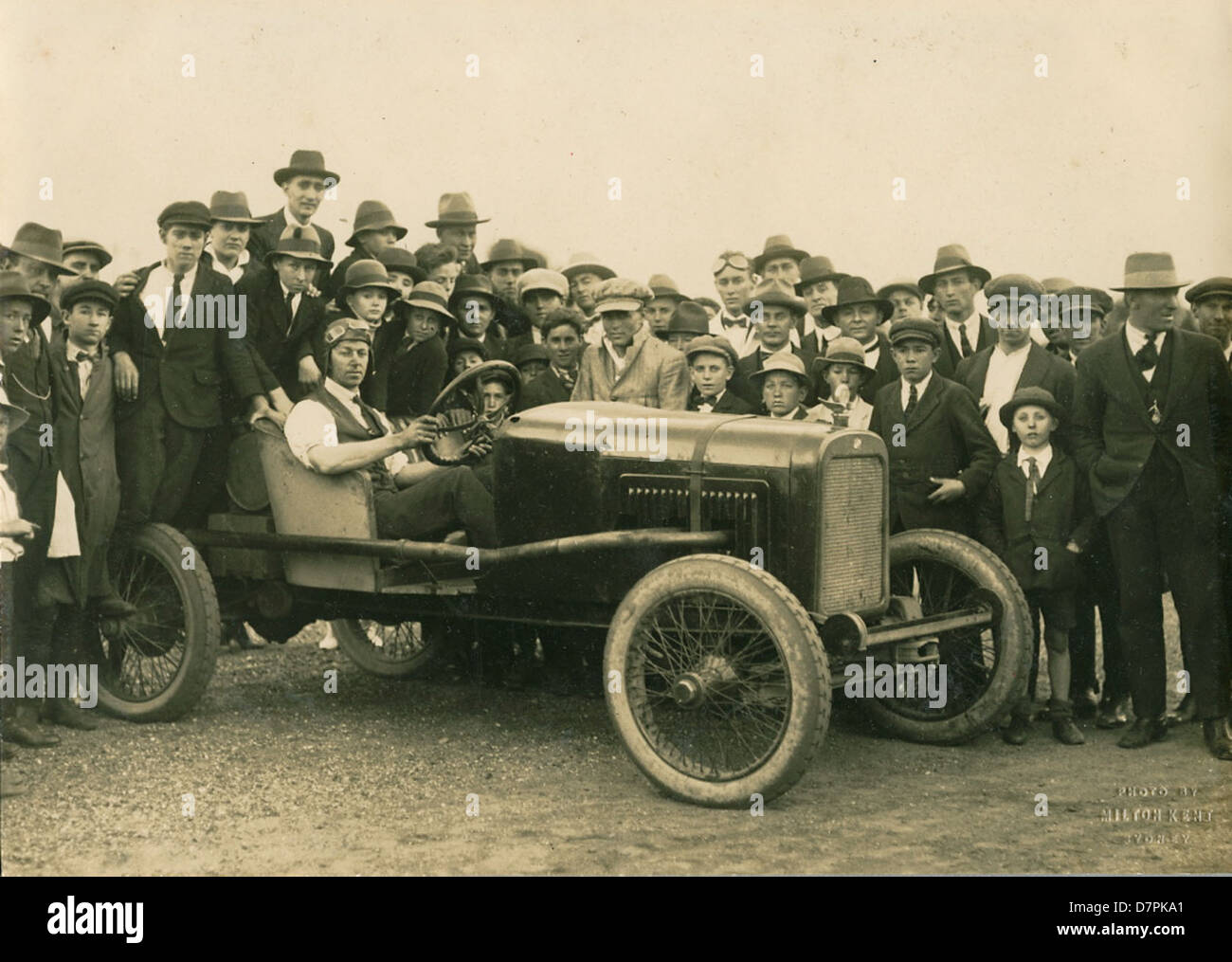 Man seated in a modified Overland racing car surrounded by crowd - Stock Image