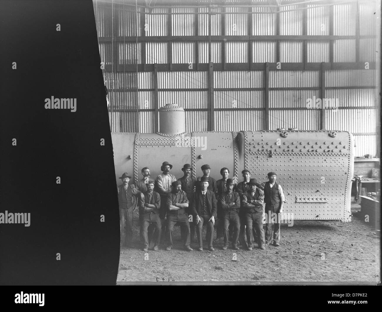 Clyde employees next to railway locomotive boiler - Stock Image