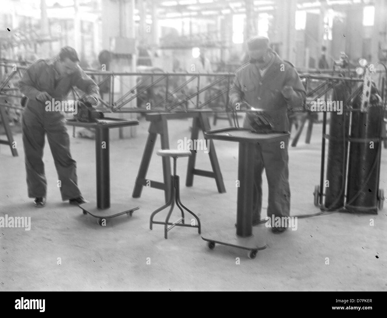 Workmen welding and filing in aircraft workshop - Stock Image